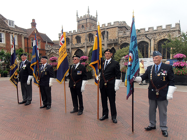 Standards from the RNA, RBL, and RAFA are paraded for Sea Sunday