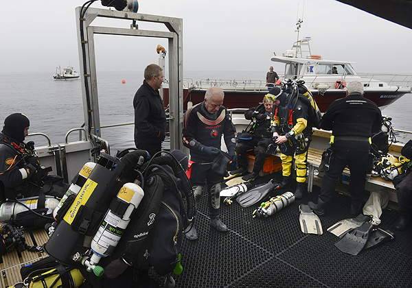 Divers prepare to lay a wreath onboard HMS Pathfinder