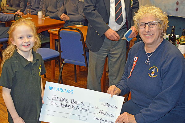 Kati Page can be seen here presenting a cheque for £600 to a youngster who attends the school