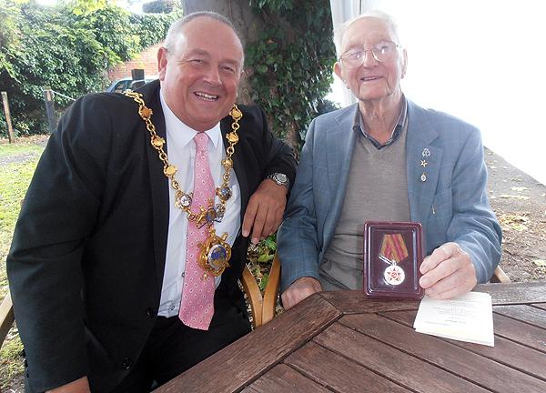 Shipmate Jack Millard shows the Mayor his medal, presented last week on behalf of Vladimir Putin